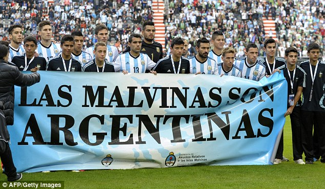 Controversial: Argentina's footballers pose for photographers holding a banner reading 'The Malvinas / Falkland Islands are Argentine' before a friendly against Slovenia