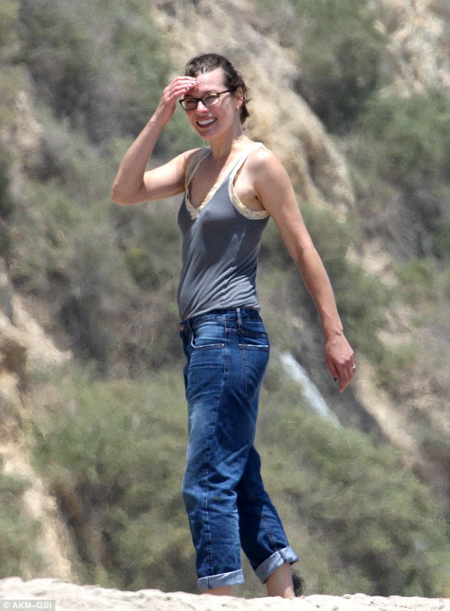 Day at the beach: The 38-year-old actress - stripped of her supermodel glamour - was dressed down in has glasses, a lacy grey vest, and boyfriend jeans