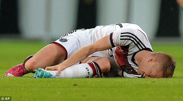 Agony: Germany star Marco Reus lies on the turf after turning his ankle in the warm-up clash against Armenia