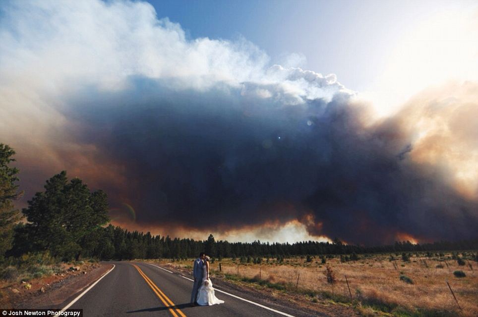 Stunning: Instead of running immediately, the couple decided to make the looming fire and smoke into a stunning backdrop to their wedding photos