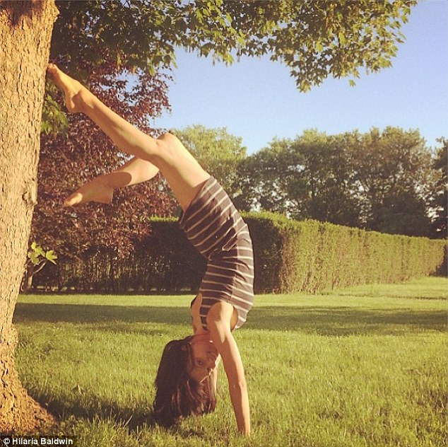 'Let's play hooky': Hilaria flashes a smile as she flips onto her hands and props her right foot against the base of a tree as her brunette hair hangs in the grass below