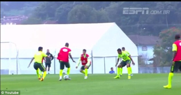 Nervy moment: Neymar (far left) rolls his right ankle while running in Brazil's evening training session