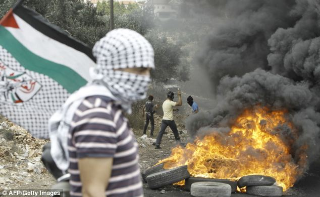 Palestinians threw stones and burned tires on Friday as they clashed with Israeli security forces about Jewish 'occupation' of Palestinian-claimed  land in the West Bank