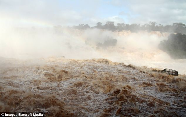 Fast flowing: Heavy rain has led to people being evacuated from their homes in World Cup host state Parana, while the Iguazu Falls (pictured) is flowing faster than ever