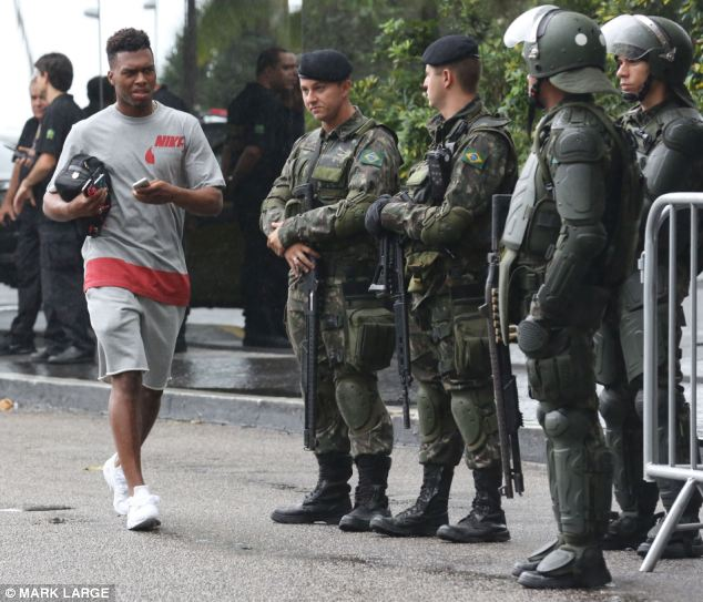 Unusual: England's Daniel Sturridge seemed confused to be walking back to the team bus past armed guards waiting to escort the players to their training camp in Rio De Janeiro