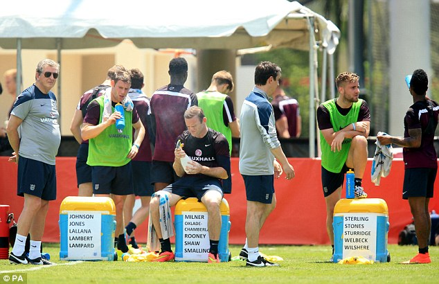 Feeling the heat: The England manager watches on as his players rehydrate during a session