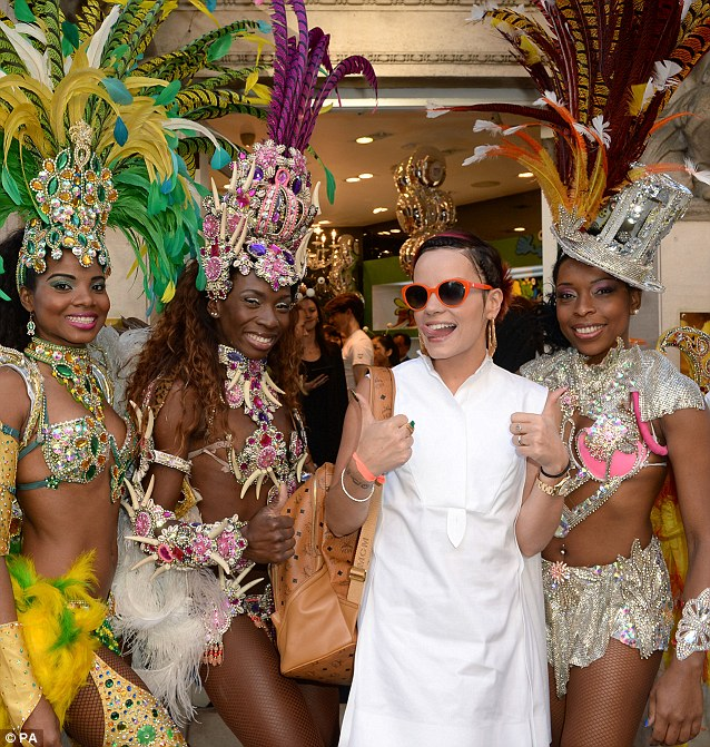Party girl: Lily looked like she was having a great time alongside the glamorous and vibrantly dressed carnival girls