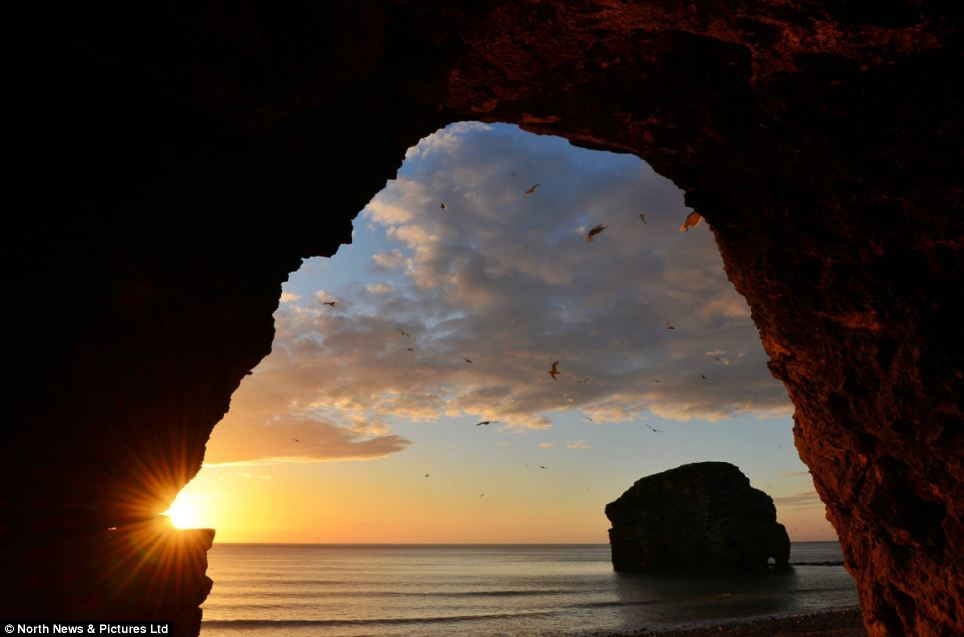 The sun emerges over the horizon in a stunning sunrise captured from a cave at Marsden beach on South Tyneside. Fine temperatures are set to last well into next week
