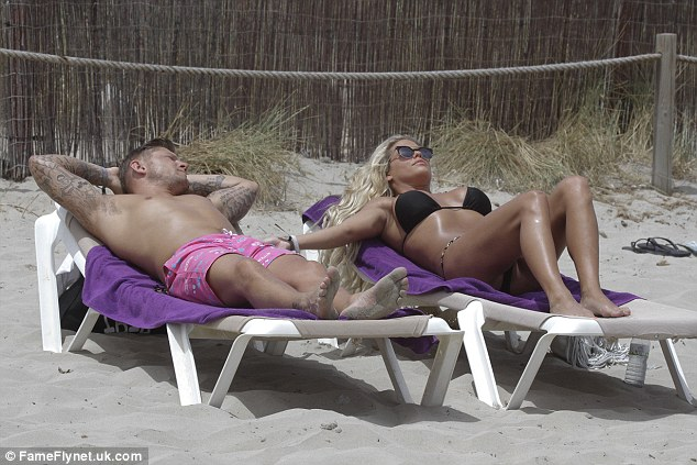 Idyllic: The couple looked thoroughly relaxed as they stretched out on sun loungers