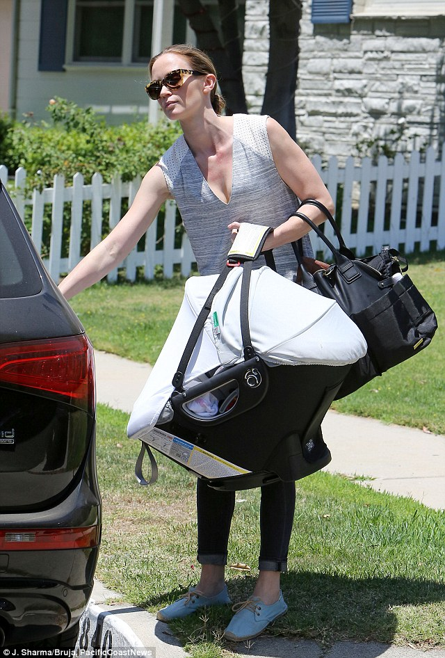 Hands full: The star was weighed down with the baby carrier and a large tote carrying all her supplies