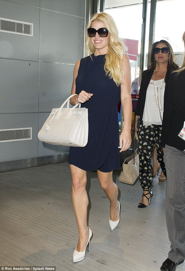 Looking good: Jessica Simpson displayed her incredibly toned legs in a navy blue frock as she made her way through JFK in NYC on Wednesday