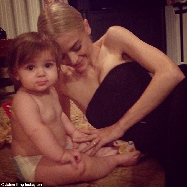 'Love is love is love....' Also on Tuesday night, the former model posted this adorable image to Instagram in which she's lying on the floor, tenderly stroking her son's arm as he sits staring at the camera, clad only in a nappy, while his famous mother is all dressed up ready to go to her event