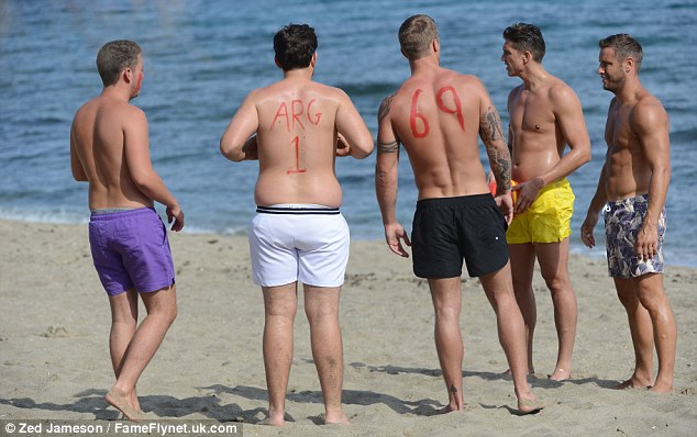 Beach football: But that wasn't the only body paint on the go as Arg had the number '1' etched on his back, while Dan had '69' painted on