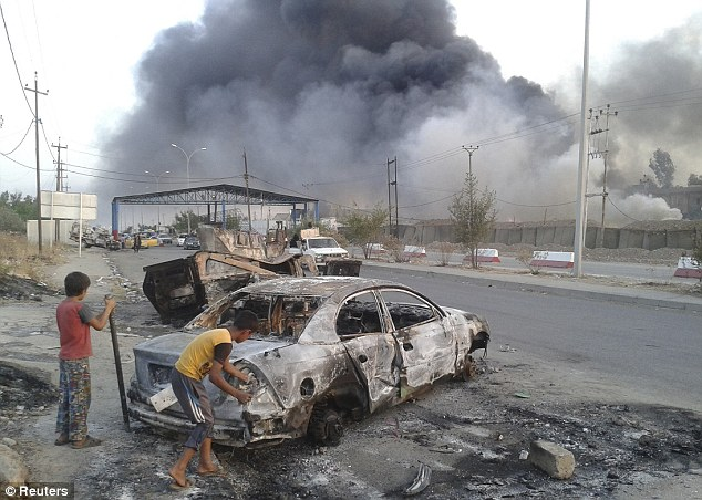 Destruction: Civilian children stand next to a burnt vehicle during clashes between Iraqi security forces and Al Qaeda-linked ISIS in the northern Iraq city of Mosul