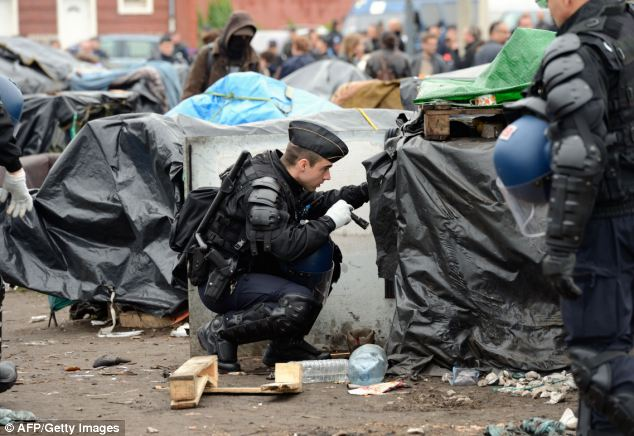 Gendarmes search the shelters of migrants in a camp at Calais on May 28. Around 35 refugees from Afghanistan and Egypt have now vowed to refuse food until a list of demands issued to Calais officials is met
