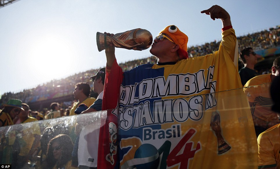 Home: A fan kisses a fake World Cup trophy ahead of the match between tournament-favourites Brazil and Croatia