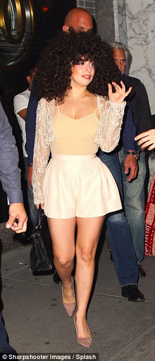 Retro: The singer seemed to be channeling the 70s as she put her slim legs on display in high-waisted cream shorts