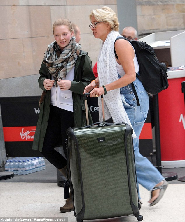 Not too famous to push: Emma was more than happy to push her own suitcase through the station