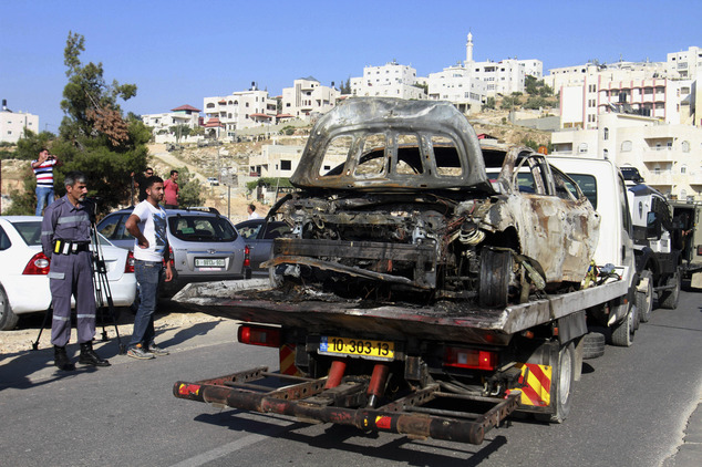A burnt car which is reportedly connected to the disappearance of three teenagers is taken away near the West Bank city of Hebron on Friday