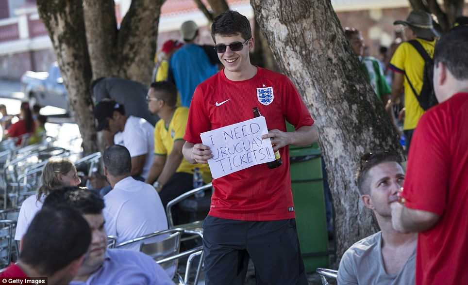 Help me out! An England fan circulates in the centre of Manaus with a sign pleading for tickets to an upcoming group clash - and an obligatory beer bottle