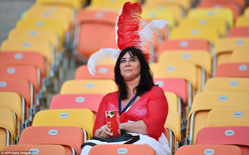 Is there something on my head? An early arrival to the stadium clutches a branded cup as she waits for the kick-off - no prizes for guessing who she supports