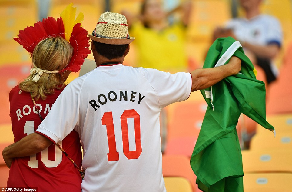 Rooney duo: A couple find their way to their seats in the Arena da Amazonia, wearing shirts which honour one of the England team's most famous names