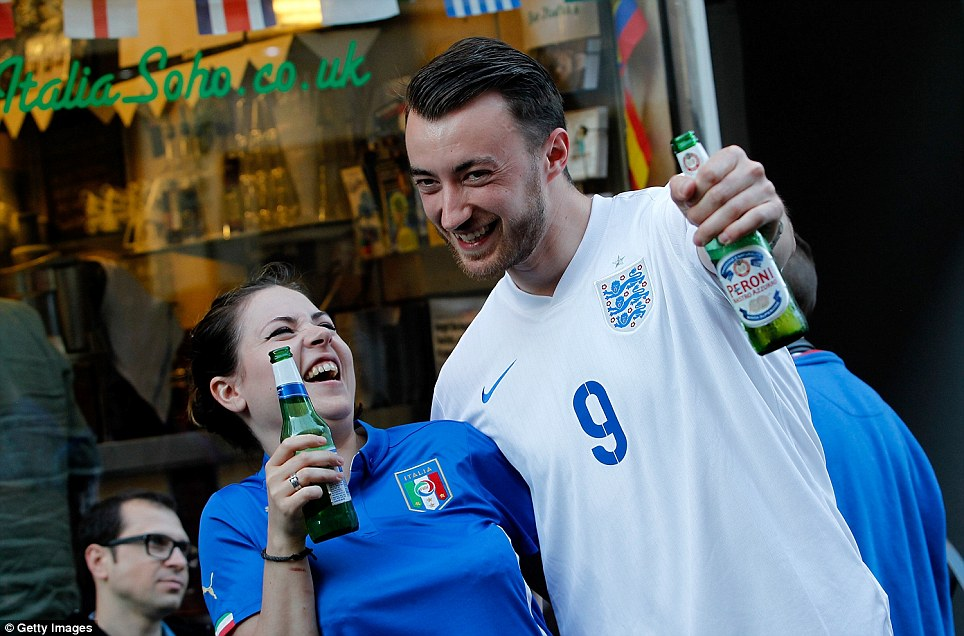 No fighting now! England fan Chris Clark and his Italian girlfriend Giulia Uccheddu gear up to watch their team take on Italy in central London - drinking Italian beer
