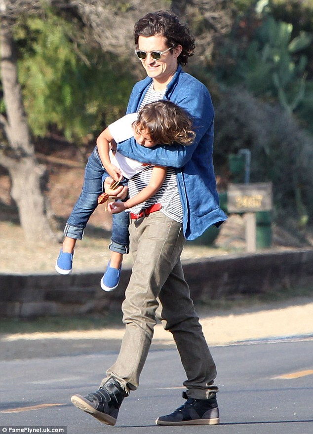 Hands-on: Orlando Bloom at first carries Flynn on his belly as they headed to a friend's house in Malibu on Saturday