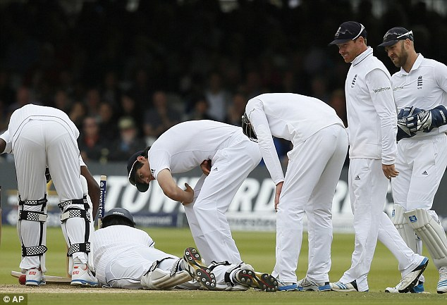 Everything ok? England's captain Alastair Cook checks on Pradeep after he fell into his wicket