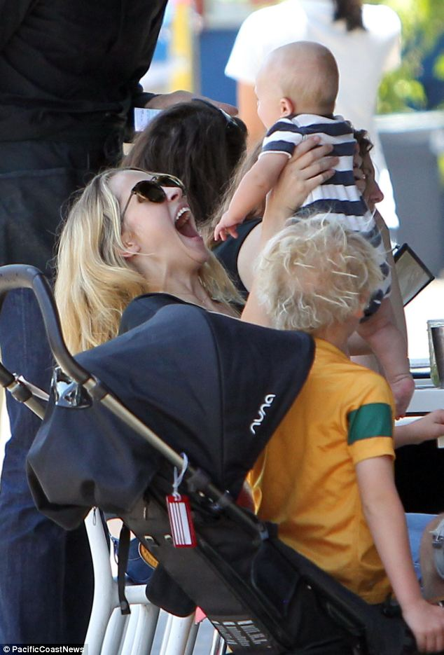 She's a natural! New mother Teresa Palmer holds baby Bodhi in the air for a sweet moment between the two during lunch at Flora Vegan Restaurant in Los Angeles