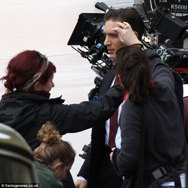 Touch up: The actor's make-up gets a bit of attention from production assistants during a break between takes on Sunday
