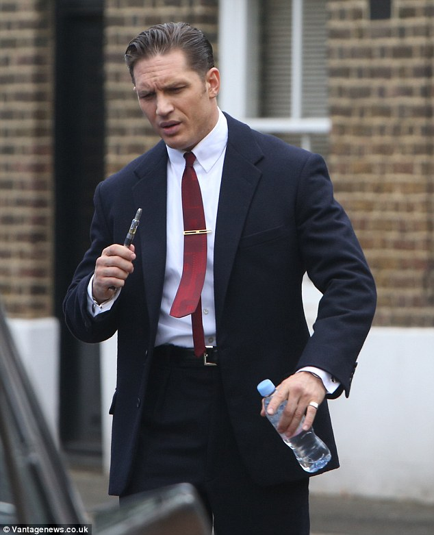 Here he comes: Tom Hardy takes a welcome break on the set of his new film, in which he plays both Ronnie and Reggie Kray