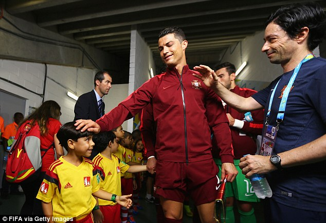 Boys from Brazil: Cristiano Ronaldo acknowledges the ball boys in the tunnel ahead of the game