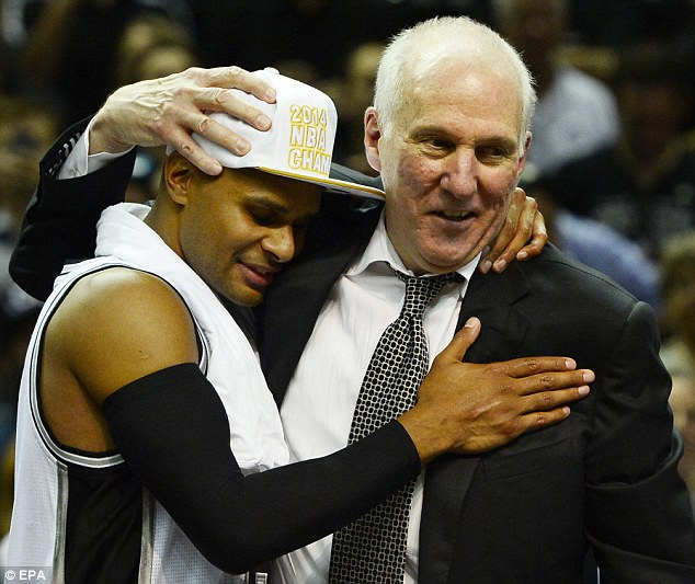 Spurs coach Gregg Popovich embraces Patty Mills (pictured right) in celebration of the victory