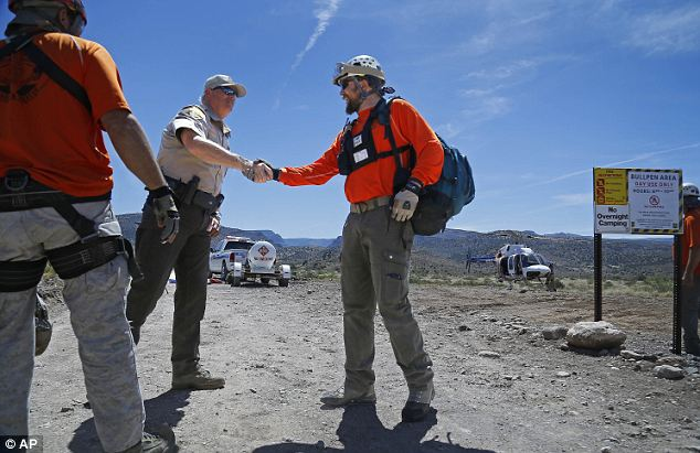 Good job: Yavapai County Sheriffs Deputy Deputy Mark Hooten congratulates Yavapai County Search and Rescue Volunteer Will Quinn. Most of the boys were able to negotiate the rough terrain and climb out to safety but the eldest member of the group was forced to stay after growing weak from his medical condition