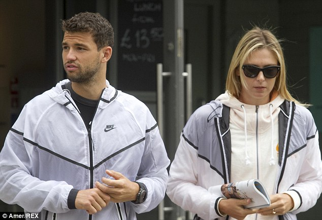 Game, set and match: Maria Sharapova and her boyfriend Grigor Dimitrov were quite literally matching on Monday as they headed out in Wimbledon wearing identical waterproof jackets