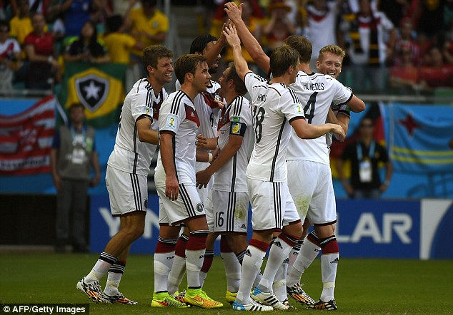 Winning with style: The German team come together to celebrate the hat-trick by Thomas Muller (left)