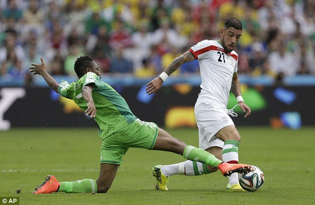 On the run: Iran wideman Ashkan Dejagah evades the tackle of Nigeria's Ahmed Musa