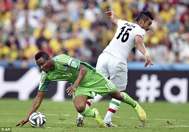 Battle: Nigeria's John Obi Mikel comes out with the ball after dispossessing Iran's Reza Ghoochannejhad