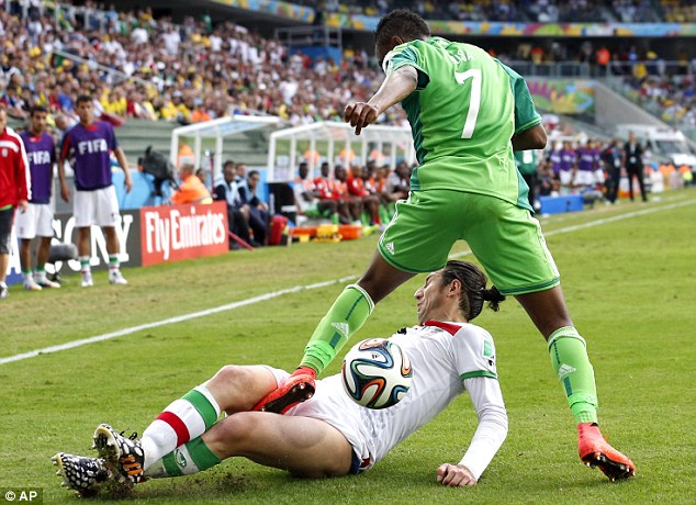 Committed: Iran's Andranik Teymourian slides under Nigeria's Ahmed Musa to take the ball away