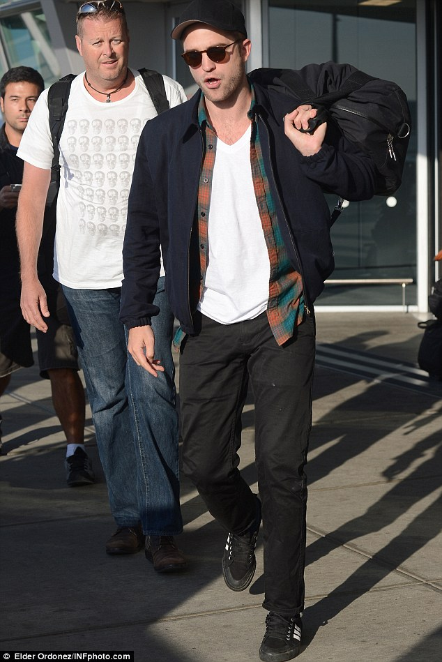 Open-mouthed: He still seemed shocked at the rumours as he headed out of JFK International Airport