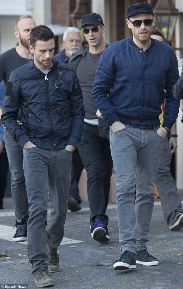 In uniform? Guy Berryman and Jonny Buckland from the band looked almost matching in navy jackets and charcoal trousers