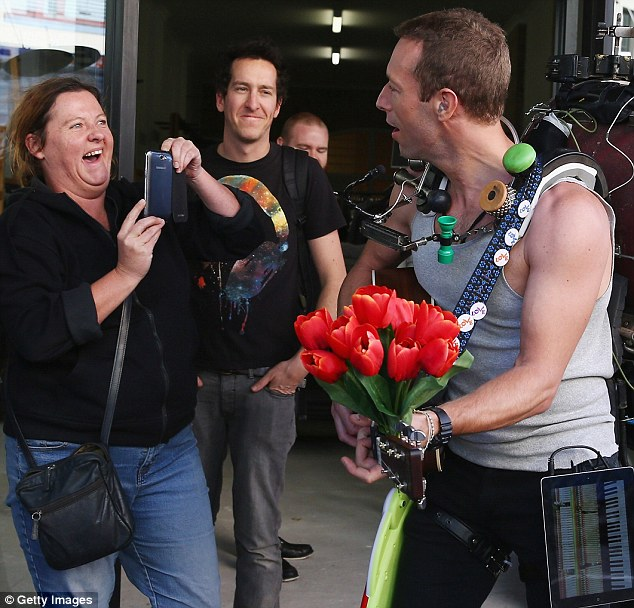 Say cheese: Chris happily stopped for a fan photo as he clutched onto the guitar embellished with red tulips