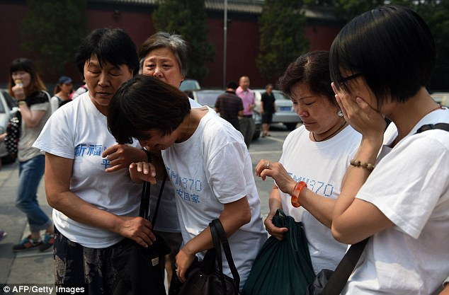 Grief: Relatives of passengers on the missing flight MH370 cry as they gather at the Lama Temple in Beijing for a memorial service on Sunday. The ceremony marked 100 days since the plane disappeared