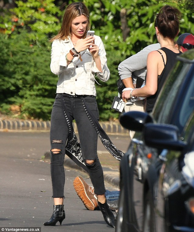Snap happy: Abbey Clancy appeared to be distracted by her phone as she took a break on a London filmset on Friday