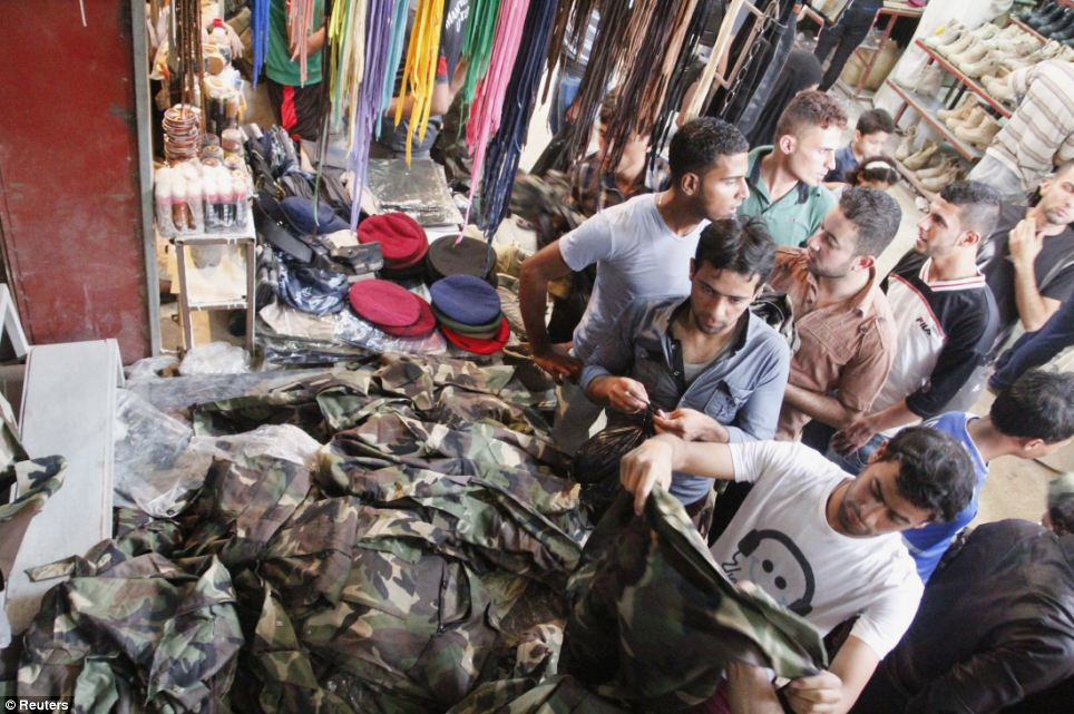 Rush to buy military clothing: Iraqi men buy military uniforms at a shop in Basra, south-east of Baghdad