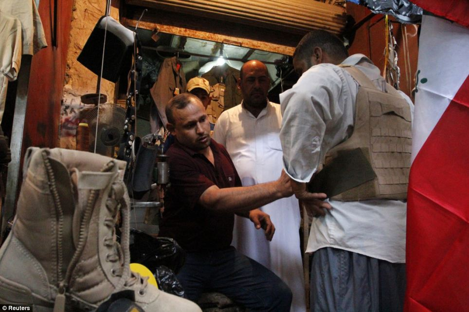 An Iraqi man (right) buys military uniforms at a shop in Basra, southeast of Baghdad
