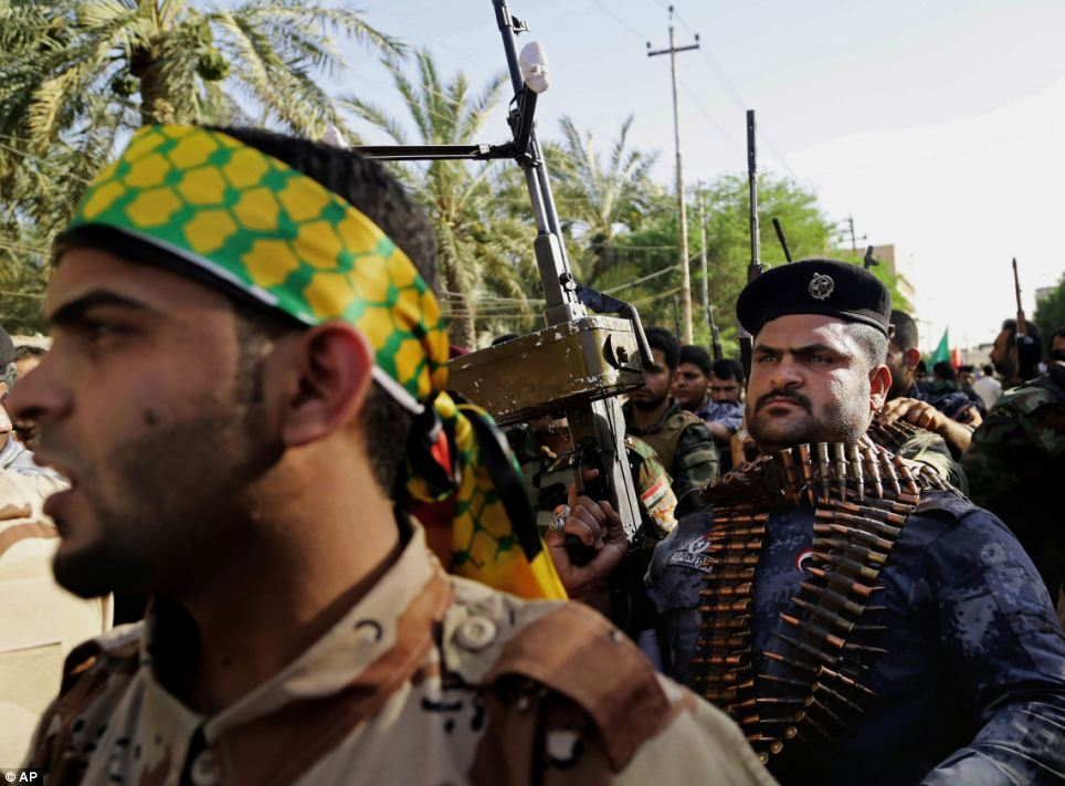 Shiite tribal fighters raise their weapons and chant slogans against the al-Qaida-inspired Islamic State of Iraq and the Levant in Basra, Iraq's second-largest city, 340 miles south-east of Baghdad