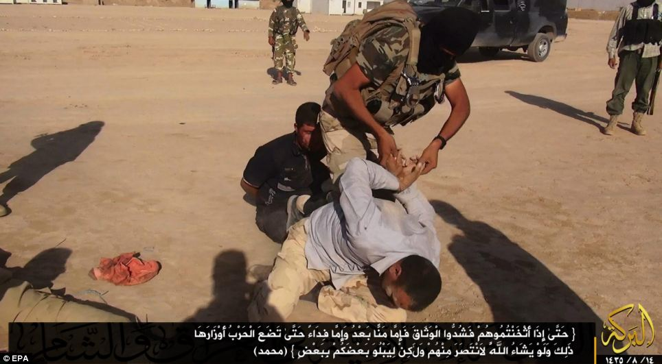 Militants tying up an Iraqi soldier captured at undisclosed location near the border between Syria and Iraq
