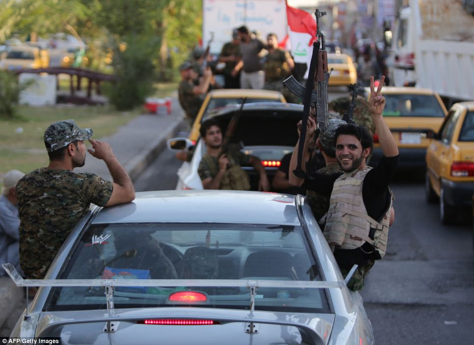 Iraqi Shiite tribesmen parade with their weapons in central Baghdad's Palestine Street as they show their willingness to join Iraqi security forces